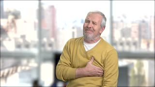 Mature man experiencing heart-attack. Aged man suffers from heart pain, window city background. Difference between heart-attack and heart arrest.