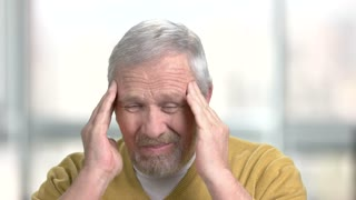 Mature man having terrible headache. Stressed senior man touching his temples because of horrible headache close up, blurred background.