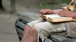 Mature man reading book. Sitting on a bench. Close up.