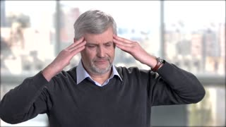 Mature man suffering from headache. Stressed senior man touching his temples because of strong head pain.