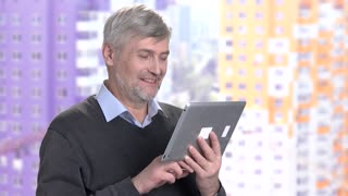 Mature man using computer tablet. Smiling man talking via interet. People and modern technology.