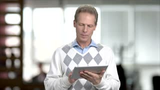 Mature man web surfing on pc tablet. Caucasian middle-aged manager working on digital tablet, blurred background.