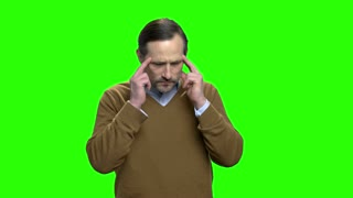 Mature man with headache. Green screen hromakey background for keying.