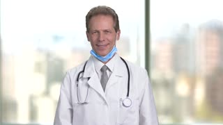 Mature middle aged smiling doctor folding arms. Bright abstract blurred windows background with view on city.