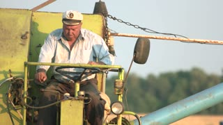 Mature redneck driving combine. Agricultaral work concept.