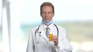 Mature smiling doctor offers can of pills. Happy physician in white coat and