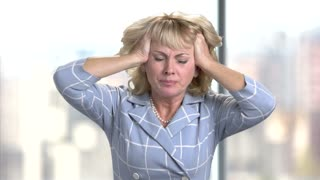 Mature woman having headache. Stressed busineswoman with headache, migraine or forgetfulness.