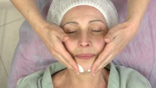 Mature woman having lymphatic massage. Hands of cosmetian, facial cream. Instant face lift.