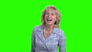 Mature woman is laughing on green screen. Middle aged female person bursting into laugh on chroma key background, slow motion.