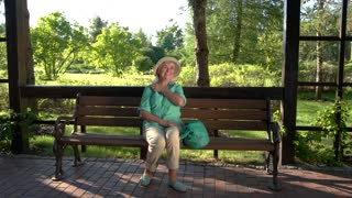 Mature woman is smiling. Lady sits on park bench. Medication has no side effects. Heart pains are gone.
