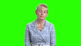 Mature woman is yawning on chroma key background. Portrait of attractive mature woman with drowsy and sleepy facial expression, yawning behind hand.