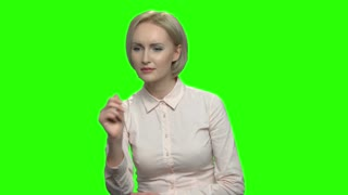 Mature woman pressing and swiping an invisible virtual screen. Green hromakey background for keying.