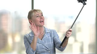 Mature woman taking video with monopod. Attractive white-skin lady waving with hand and smiling to selfie stick in studio.