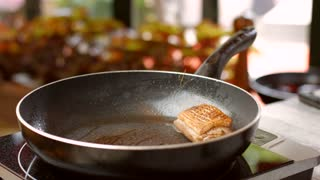 Meat and herbs on pan. Bottle pours liquid on meat. Chef is preparing duck steak. Delicious meat with garlic.