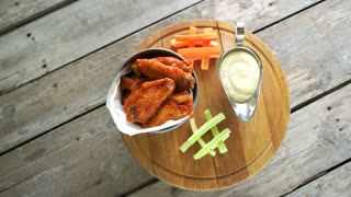 Meat appetizer with sauce. Fried chicken wings in bucket.