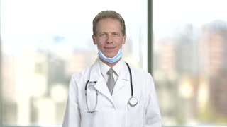 Medical doctor showing thumb up gesture. Smiling man doctor with protective mask under chin showing thumb up, blurred background.