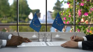Men are signing papers. Businessmen shake hands at desk. It's time for changes. Leaders of European Union.