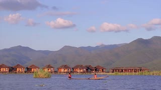 Men rowing the oars on a wooden canoe. Water transport. Beautiful nature of Inle Lake.