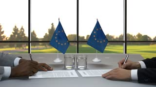 Men sign papers. Handshake of businessmen at desk. New laws come in force. Meeting of EU leaders.