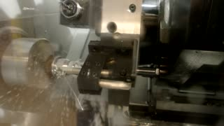 Metal lathe in action. Machine and water splashing.