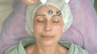 Microcurrent face treatment, adult female. Hands of cosmetician using tool.