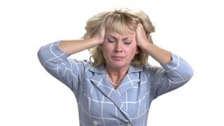 Middle age woman with headache touching her head. Terrible head pain. Extremely tired and stressed mature woman in white isolated background.