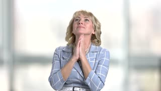 Middle-aged blonde is dreaming on blurred background. Happy smiling woman with clasped hands closed her eyes.