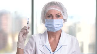Middle aged doctor holding a syringe. Mature caucasian female surgeon with mask, hair cap, gloves, surgeon cloth indoor.