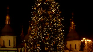 Middle of the flashing christmas tree. Orthodox church in the background.
