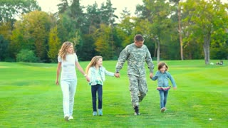 Military man and family walking and having fun. Handsome caucasian soldier reunited with family on a sunny day in the park.