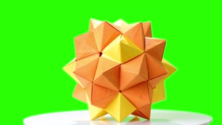 Modular origami flower on green screen. Yellow origami ball on chroma key background. Paper folding and geometry.