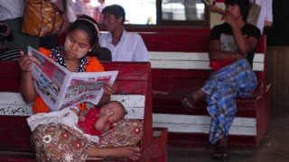 Mother and baby at the station. Mom reading a newspaper while waiting of the train. Baby sleeps on the mother hands. Poor country. Refugees at the station.