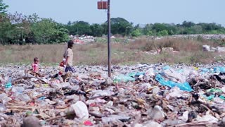Mother with kids looking for food in a landfill. Poor people. Poor family walking on the heaps garbage.