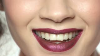 Mouth of girl smiling, makeup. White teeth and red lipstick.