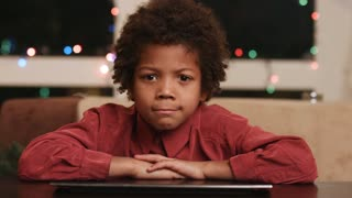 Mulatto boy playing the ape. Kid grimacing at computer table. Sudden change of face expression. Young funny actor on Christmas.