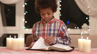 Mulatto boy turning book pages. Kid with book on Christmas. Interesting fairy tale book. Child reading on Christmas eve.