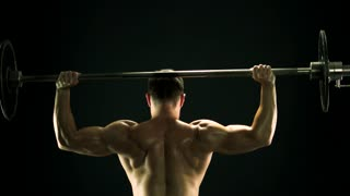 Muscular man lifting barbell, back view. Rear view sweaty muscular sportsman lifting heavy weight on dark background. Professional bodybuilding concept.