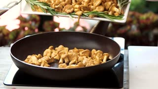 Mushrooms are falling in slow-mo. Golden chanterelles in frying pan. Autumn food recipes.