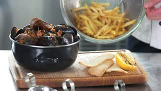 Mussels and fries. Food on a wooden board.
