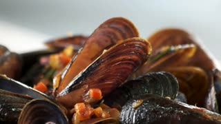 Mussels with vegetables and rosemary. Steamed clams macro.
