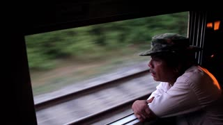 Myanmar, Yangon. 13/11/2013. Asian man traveling in the train. Railway. Man looks out the window of the train.