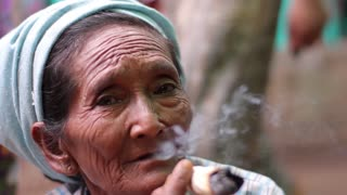 Myanmar, Yangon. 15/11/2013. Old woman with cigar. Close-up of an old woman. Asian grandmother smokes.