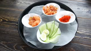 Natural food ingredients in bowls. Sliced cucumber, egg and salmon.