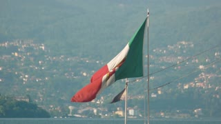 Naval ensign of Italy. Italian flag, Stresa town background. European citizenship program.