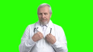 Nervous sad doctor portrait. Senior old physician sad about patient death. Green screen hromakey background for keying.