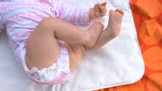 Newborn girl lying on carpet. Bare legs of sweet newborn girl. Health and skin care of infants.