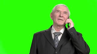 Old businessman talking on phone. Portrait of senior businessman in suit talking on phone, green hroma screen background.