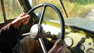 Old car goes through the countryside. Steering wheel of retro car. Before military vehicle. Old military truck.