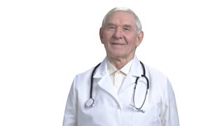 Old caucasian doctor in white isolated background. Senior doc in white medical coat with stethoscope.