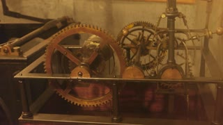 Old clock mechanism in motion. Cogwheels and pendulum.